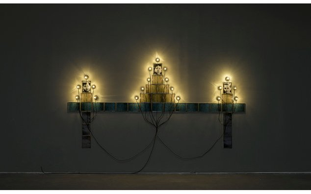 Monument 1986 / Photographs, frames, sockets, light bulbs and black electric wires / Collection of the artist (Christian Boltanski — Lifetime)